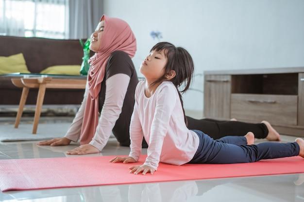 Aziatische moslimvrouw en dochter die oefening en sport thuis doen tijdens zelfisolatie