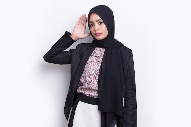 Aziatische moslimvrouw houdt haar hand bij haar oor en luistert