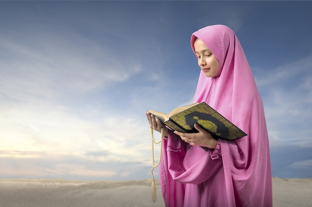Aziatische moslimvrouw in een sluier die bidparels houdt en de koran leest met een blauwe hemelachtergrond