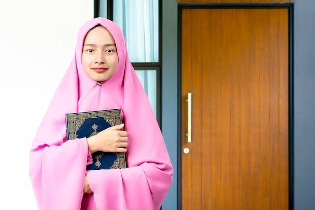 Aziatische moslimvrouw in een sluier die de koran voor het huis staat en vasthoudt