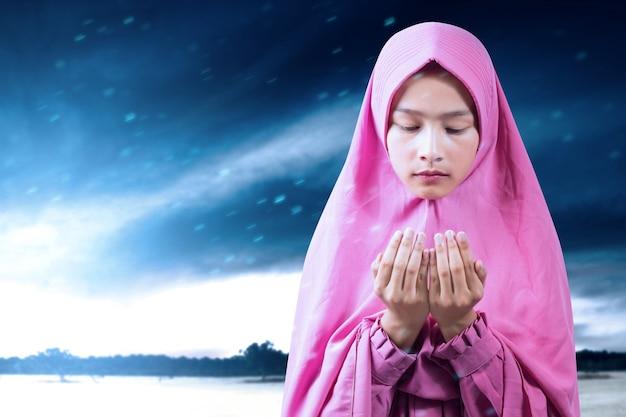 Aziatische moslimvrouw in een sluier staande terwijl opgeheven handen en bidden met dramatische hemelachtergrond