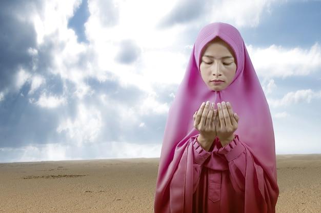 Aziatische moslimvrouw in een sluier staande terwijl opgeheven handen en bidden met een blauwe hemelachtergrond