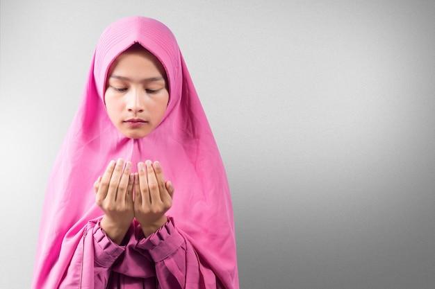 Aziatische moslimvrouw in een sluier staande terwijl opgeheven handen en bidden met mist achtergrond