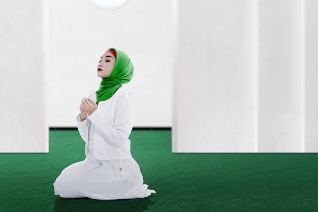 Aziatische moslimvrouw in een sluier zittend terwijl opgeheven handen en bidden op de moskee