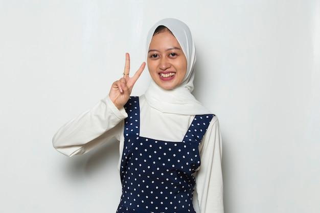 Aziatische moslimvrouw in hijab die vrede of overwinningshandgebaar toont