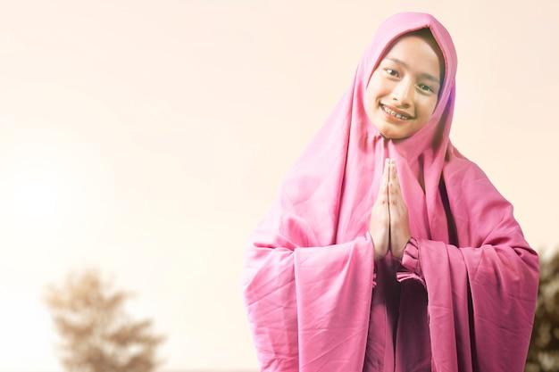 Aziatische moslimvrouw in sluier met groetgebaar met een zonsopganghemelachtergrond