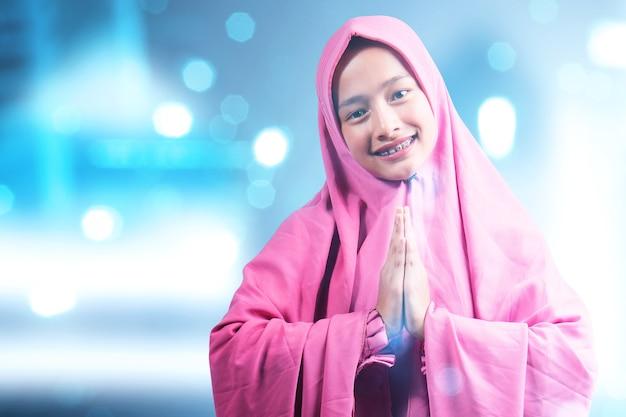 Aziatische moslimvrouw in sluier met groetgebaar met onscherpe lichte achtergrond