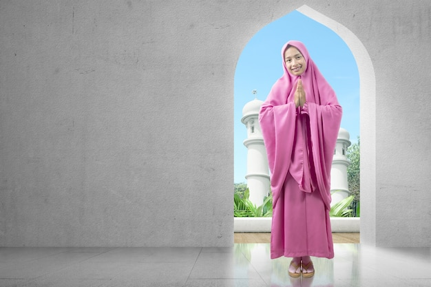 Aziatische moslimvrouw in sluier met groetgebaar op de moskee