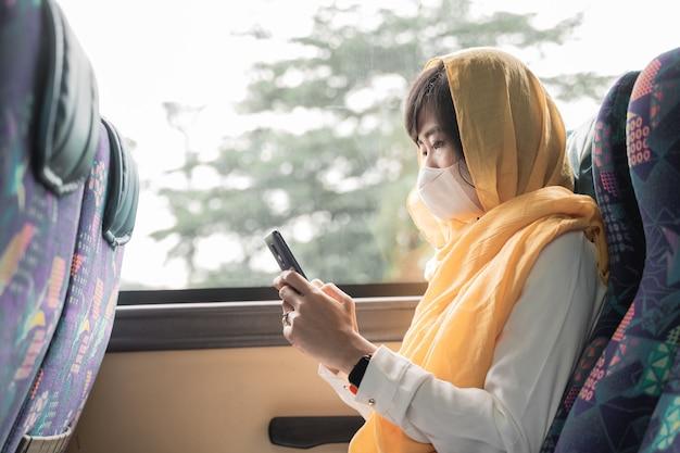 Aziatische moslimvrouw met gezichtsmasker met behulp van haar mobiele telefoon tijdens het rijden in een bus