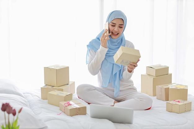 Aziatische moslimvrouw met veel dozen in bed