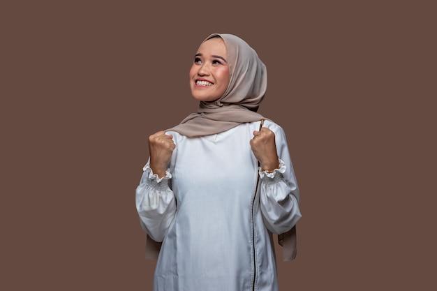 Aziatische moslimvrouw poseren om succes te vieren door haar handen op te steken