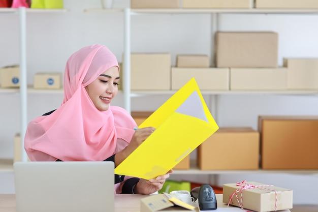 Aziatische moslimvrouw zit en houdt map vast met computer en online pakketdoos