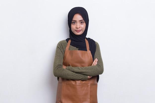 Aziatische moslimvrouwenbarista-serveerster die schort op witte achtergrond draagt