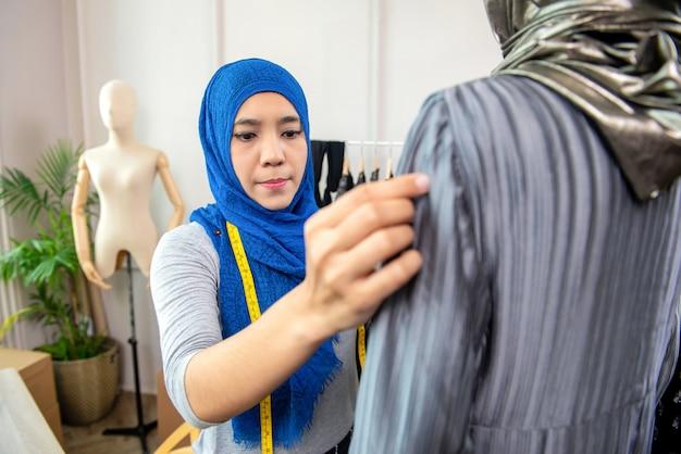 Aziatische moslimvrouwenontwerper die in haar kleermakerswinkel werken