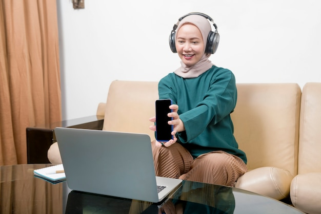 Aziatische moslimzakenvrouw die een laptop gebruikt die vanuit huis werkt. voorkom griepziekte coronavirus