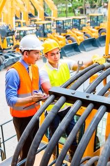 Aziatische motor monteur bespreken met de takenlijst van de ingenieur in de werkplaats van de machine van de bouw