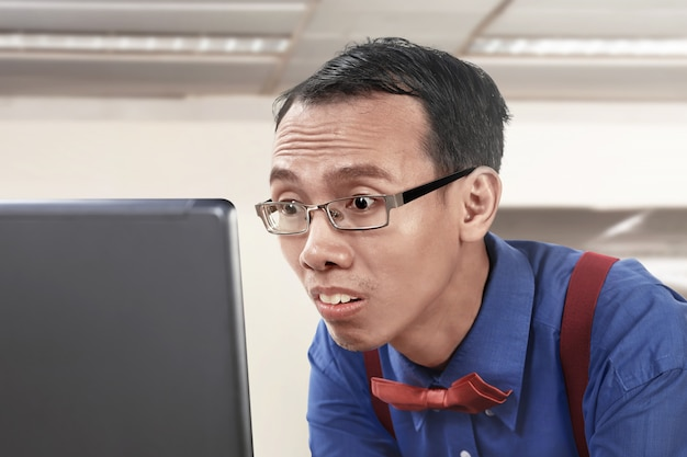 Aziatische nerdy zakenman die gebruikend laptop werkt