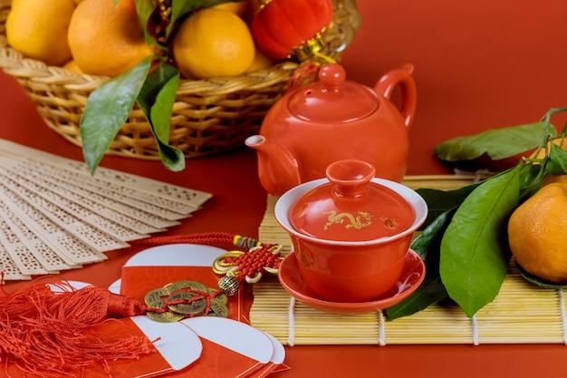 Aziatische nieuwe maanjaarvieringen met ceremonietheeset op bamboe en mandarijn sinaasappelen a op rood