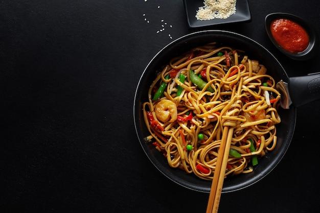 Aziatische noedels met garnalen en groenten geserveerd op pan op donkere achtergrond.
