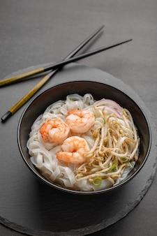 Aziatische noedels met garnalen en zeevruchten in zwarte kom
