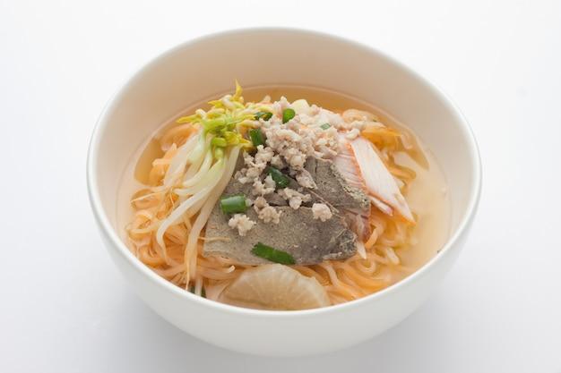 Aziatische noedels met kip, groenten in kom, rustieke houten.