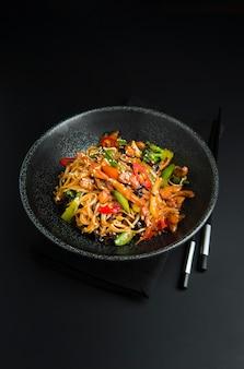 Aziatische noedels met kip, groenten in zwarte kom en eetstokjes. aziatisch eten stijl