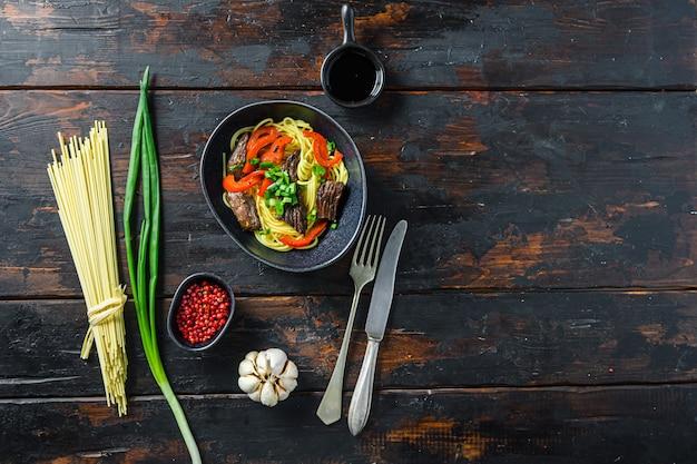 Aziatische noedels met rundvlees, bovenaanzicht over oude houten tafelruimte voor tekst.