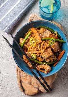 Aziatische noedels met varkensvlees in teriyakisaus, met sperziebonen, wortelen en shiitake-paddenstoelen. bovenaanzicht.