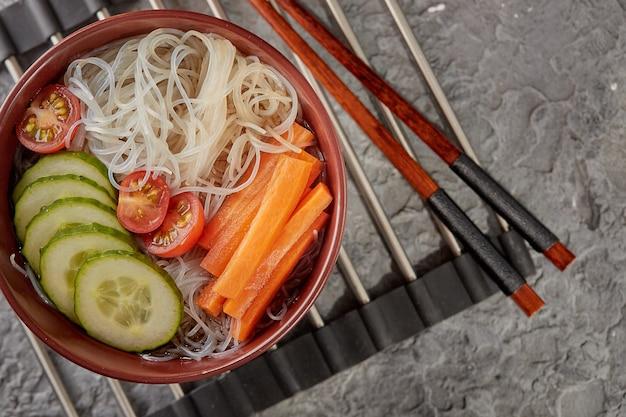 Aziatische noedelsoep, ramen met groenten in een kom op een standaard voor warme gerechten.