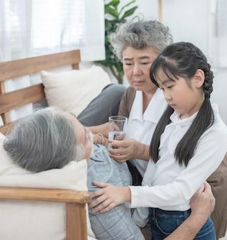 Aziatische oma en kleindochter zorgen voor en zorgen ervoor dat opa glas water geeft met medicijnen