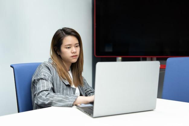 Aziatische onderneemster die aan laptop in een bureauruimte werkt met geïrriteerde en ontevreden emotie