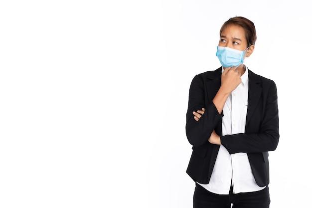 Aziatische onderneemster die chirurgisch gezichtsmasker in zwart kostuumjasje draagt stelt als denken