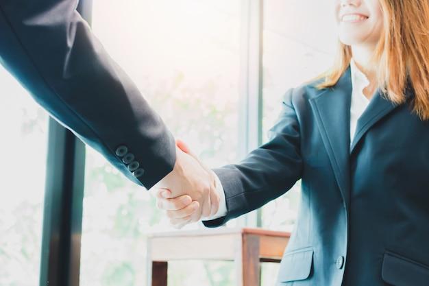 Aziatische onderneemster die handdruk met een zakenman maken - groet en de handelsconcepten
