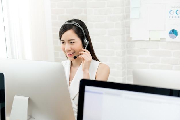 Aziatische onderneemster die hoofdtelefoon draagt die in call centre werkt