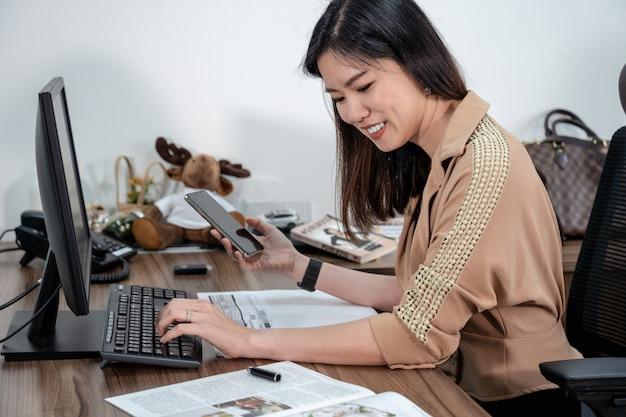 Aziatische onderneemster die in formeel kostuum en met computer en mobiel in bureau, bedrijfs en projectplan schrijven voor het concept van de klantendienst