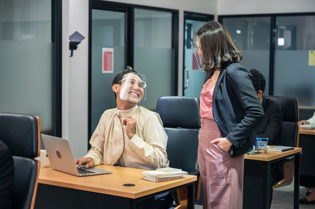 Aziatische onderneemster die met gelukkige en glimlachende homo-collega overlegt die gezichtsscherm draagt bij bureau in modern bureau