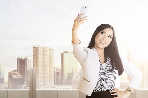 Aziatische onderneemster die selfie gebruikend de camera van haar telefoon op het bureauterras maken