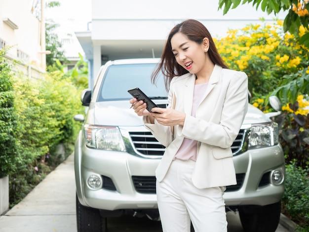 Aziatische onderneemster die slimme telefoon met behulp van tegen een auto.
