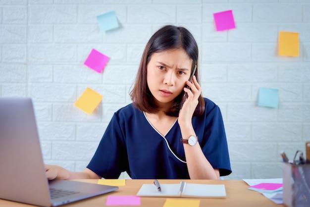 Aziatische onderneemster die smartphone met het voelen van spanning van het harde werk lange tijd in de ruimte van het bureaukantoor gebruiken.