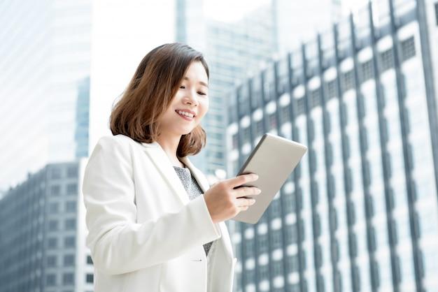 Aziatische onderneemster die tabletcomputer in openlucht bij de bouw van het onduidelijk beeldkantoor met behulp van
