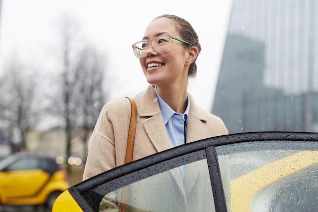 Aziatische onderneemster die taxi nemen in regenachtige straat