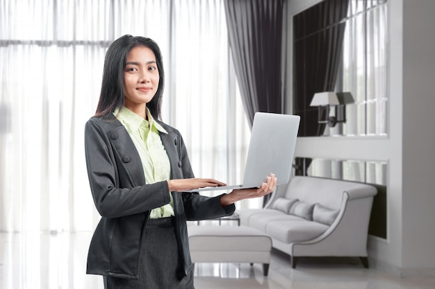 Aziatische onderneemster die zich terwijl het gebruiken van laptop die van huis werken bevinden