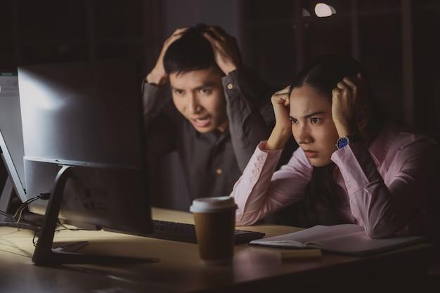 Aziatische onderneemster en zakenman die laat hard samen met technologiecomputer werken in bureau