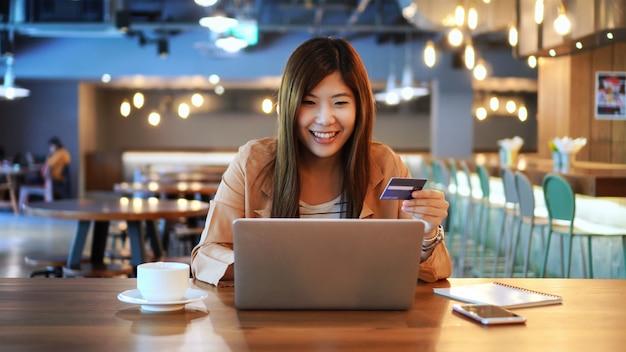 Aziatische onderneemster in toevallige reeks die de creditcard met computer met behulp van