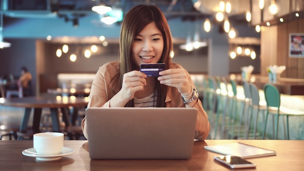 Aziatische onderneemster in toevallige reeks die de creditcard met computer voor online het winkelen gebruikt