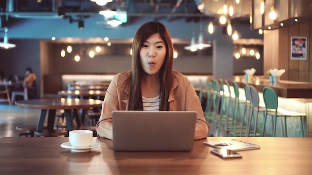 Aziatische onderneemster in toevallige reeks met verrassend of wow gevoel wanneer de status controleert