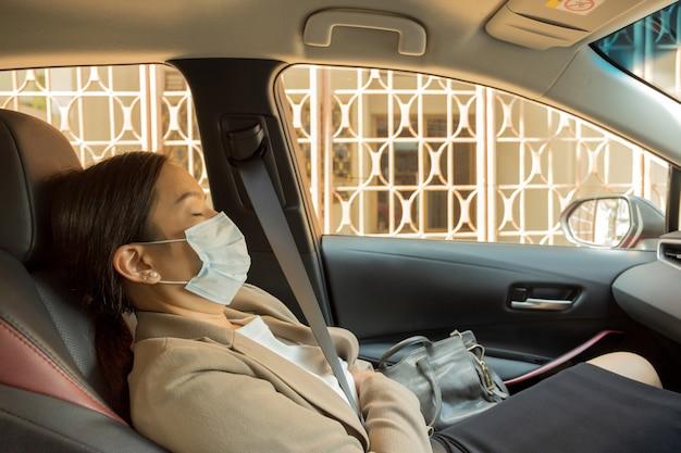 Aziatische onderneemster met beschermend masker om van covid te bewijzen - leggend 19 in auto leggen.