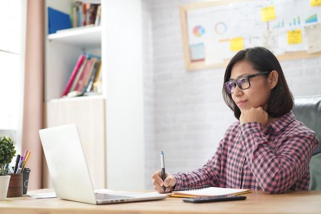 Aziatische onderneemsterlezing op laptop computer