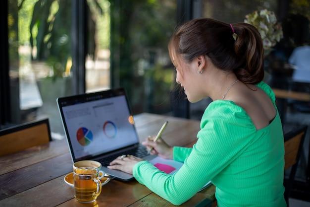 Aziatische onderneemsters die en notitieboekje voor analysedocumenten en grafiek het financiële diagram werken glimlachen gebruiken en zij drinkt koffie bij koffiewinkel