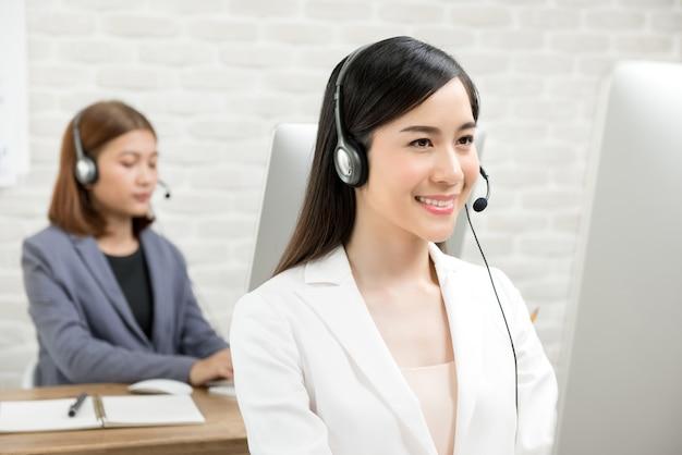 Aziatische onderneemsters die hoofdtelefoons dragen